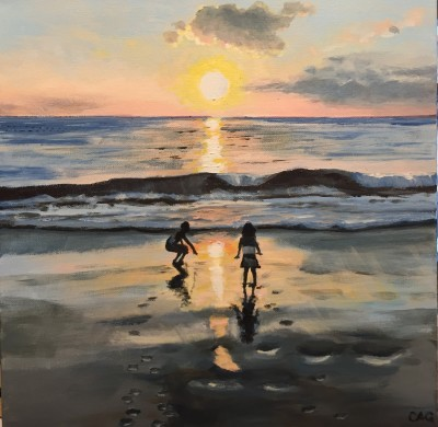 Kids playing on beach at sunset