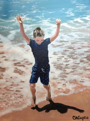 Boy standing in shallow water on sand with arms in the air